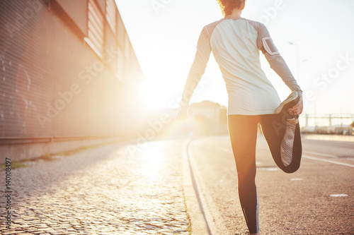 Athlete woman preparing for running on the city street. Legs warming and stretching. Sport tight clothes. Bright sun, blurry background. Horizontal