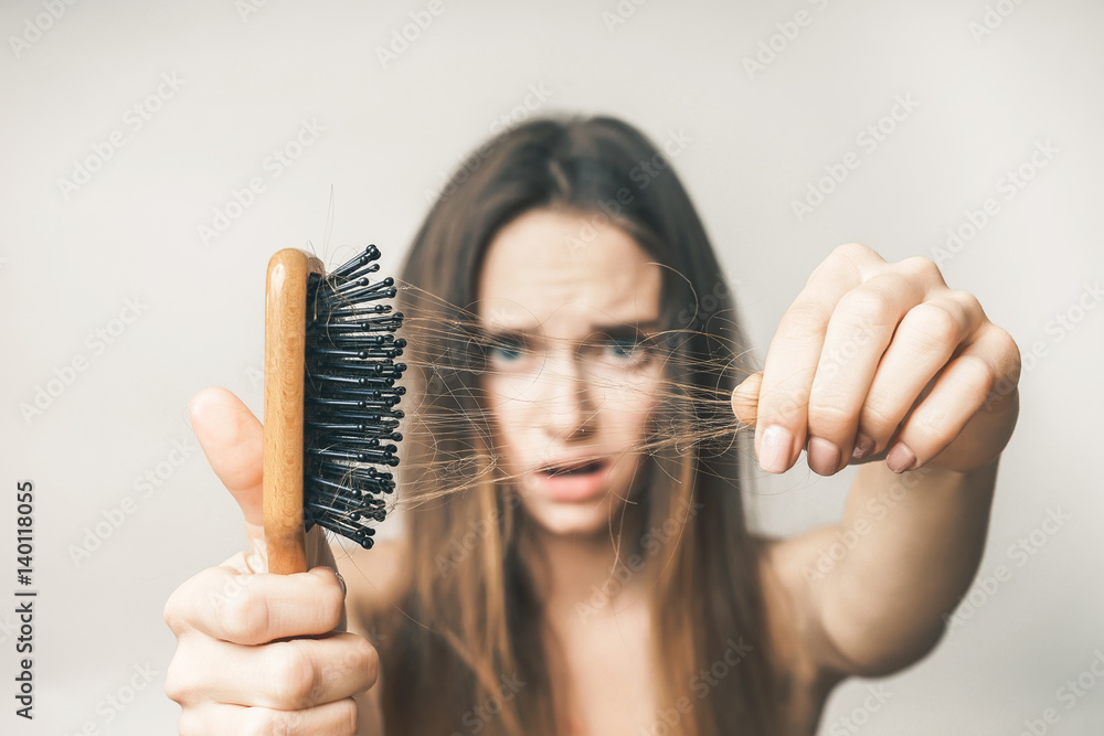 Fototapeta Woman with hair comb loss hairs close up