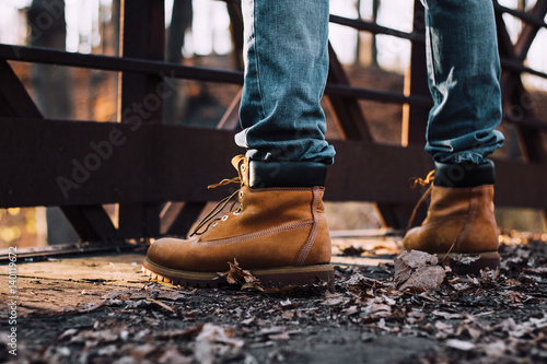 Fotografiet man wearing boots standing on bridge