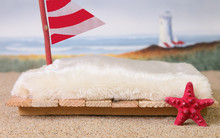 A Raft On The Sand With A Red Starfish, Red And White Sail And A Lighthouse And Ocean Waves In The Background.  This Image Can Be Used As A Newborn Photography Prop.