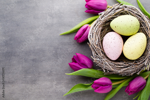 Plakat Wiosna z życzeniami. Wielkanocni jajka w gniazdeczku. Wiosenne kwiaty tulipany.