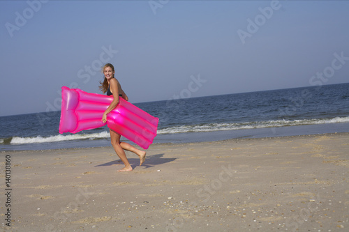Fototapeta  Young woman carrying an airbed at the beach