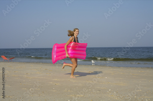 Obraz na plátně  Young woman carrying an airbed at the beach
