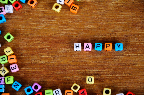 Fotografia, Obraz  Word HAPPY printed on small plastic cubes and surrounded by plastic block with colorful alphabet printed on it