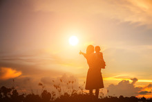 A Silhouette Of A Happy Young Girl Child The Arms Of His Loving Mother For A Hug, In Front Of The Sunset In The Sky On A Summer Day.