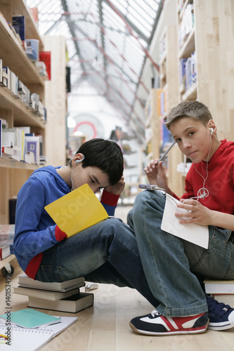 Two boys reading in a library and listening to music by MP3