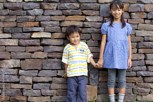 Foto op Aluminium Wand Portrait of girl and boy standing by brick wall, hand in hand