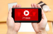 Watching two hand holding mobile phone with play and share icon on screen and blur desk office background,Digital content concept