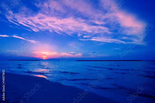 Fotobehang Donkerblauw Early morning, sunrise over sea. Blue pink beautiful sunrise. Twilight time on the beach.