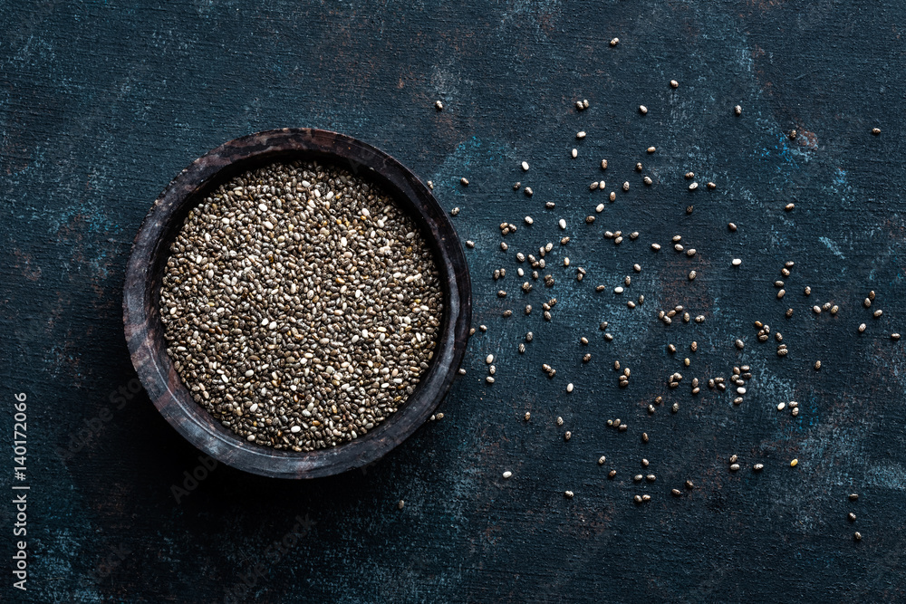 Fototapety, obrazy: Chia seeds in a stone bowl on a dark background