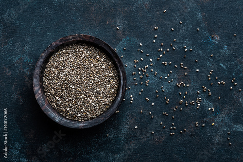 Chia seeds in a stone bowl on a dark background