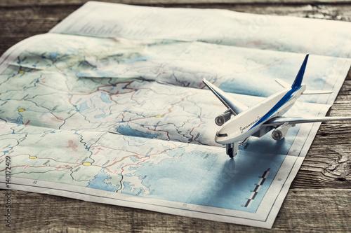 zabawkowy-samolocik-lezacy-na-papierowej-mapie-swiata