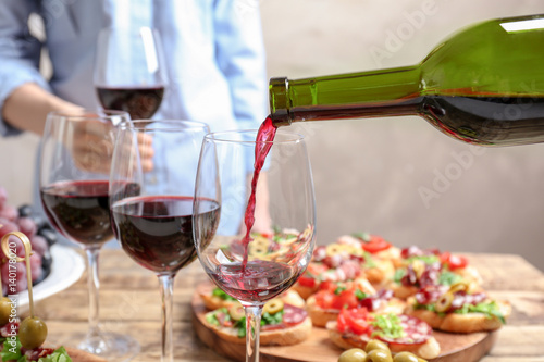 Fotografie, Obraz  Pouring red wine into glass at lunch time