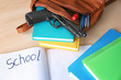School backpack with books, stationery and gun on desk