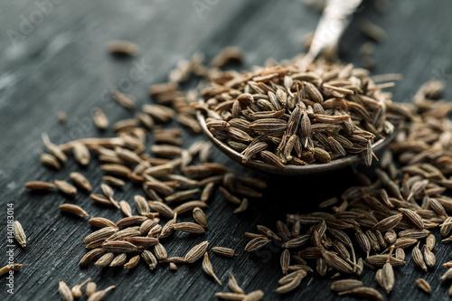 Fototapeta Cumin seeds in metal spoon on a wooden table, horizontal, selective focus obraz
