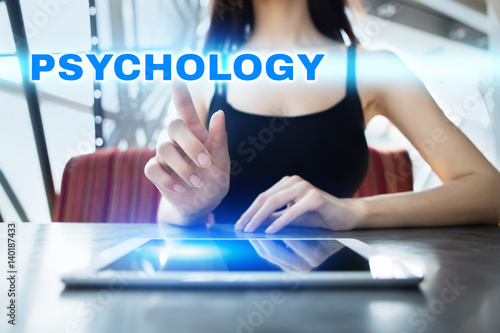 Valokuva  Woman is using tablet pc, pressing on virtual screen and selecting psychology