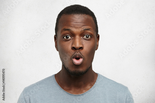 Fotografija  Close up shot of funny young African American man dressed casually pouting lips