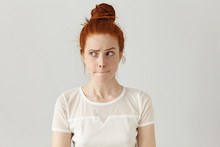 Indoor Shot Of Cute Redhead Girl Looking Away, Having Doubtful And Indecisive Face Expression, Pursuing Her Lips As If Forbidden To Say Anything. Confused Young Female Posing Isolated At White Wall
