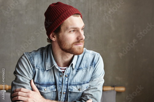 Fotografía  Bearded hipster of European appearance wearing denim jacket and stylish hat wait