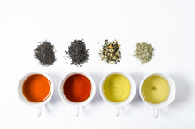 Collection Of Different Teas In Cups With Tea Leaves On A White Background