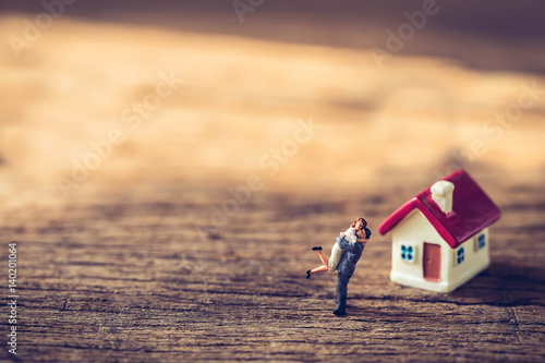 Fotografie, Obraz  miniature couple and miniature house with red roof on wooden mock up on day noon light
