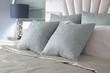 Light blue satin finished pillows on bed and black reading lamp in background