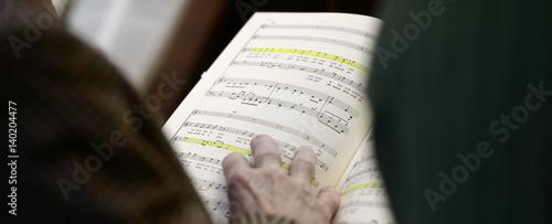 Valokuvatapetti Hand und Noten bei Chorprobe