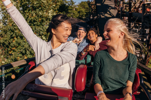 Foto auf Leinwand Vergnugungspark Friends enjoying and cheering on roller coaster