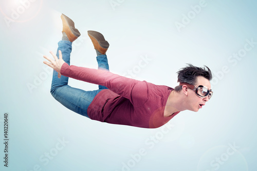 Photographie Crazy man in goggles is flying in the sky. Jumper concept