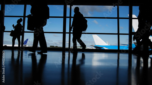 Photo Travellers with suitcases and baggage in airport walking to departures in front