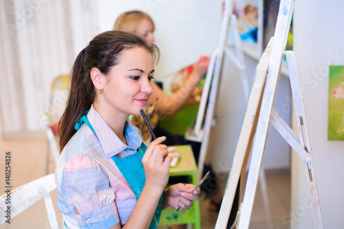 Obraz na płótnie beautiful young girls draws a picture paints on art lesson