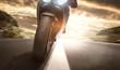 Motorrad fährt auf einer Landstraße bei Sonnenuntergang