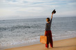 Back view of blurry woman holding suitcase on the sea beach outdoors background. Traveler discovering journey, exploring escape or journey opportunities. Sunny water