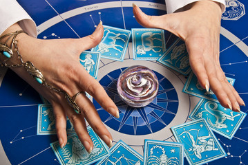 fortune teller astrologer with esoteric tools cards, zodiac signs, horoscope and stones