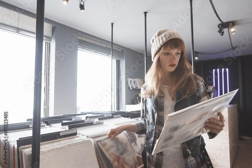 Spoed Foto op Canvas Muziekwinkel beautiful young woman audiophile is browsing vinyl records in a store