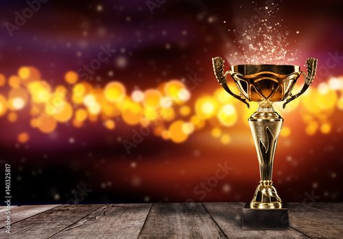 Leinwand Poster Champion golden trophy on wood table with spot lights on background
