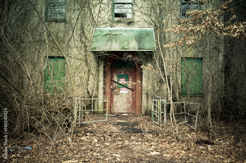 View of exterior of abandoned psychiatric hospital with asbestos warning on door Canvas Print