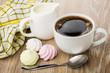 Black coffee, meringues, milk in jug, spoon and napkin