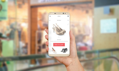 Shopping online with modern phone with round edges. Woman holding phone. Shop in background.