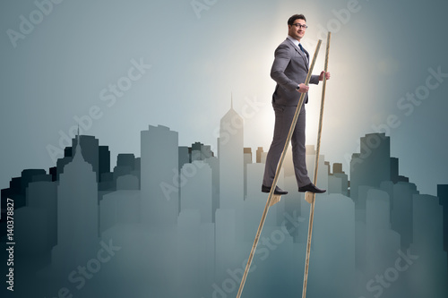Tablou Canvas Businessman walking on stilts - standing out from the crowd