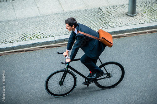 Valokuva  Young man wearing business suit while riding an utility bicycle