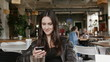 Stylish young woman uses a smartphone surf the internet sitting at a table in modern cafe, smiling. 4K