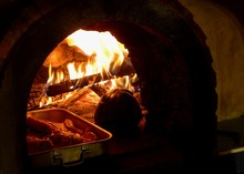 Wood Fire Oven Roaring With A Pumpkin And Delicious Meat Tray Cooking Away Slowly.