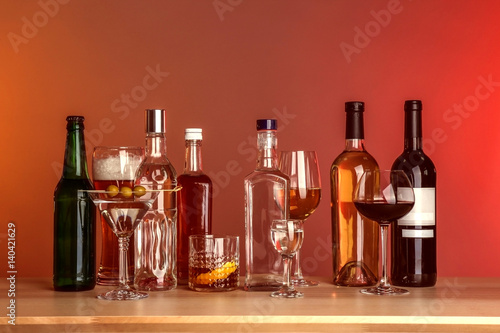 Poster de jardin Bar Table with different bottles of wine and spirits on color background