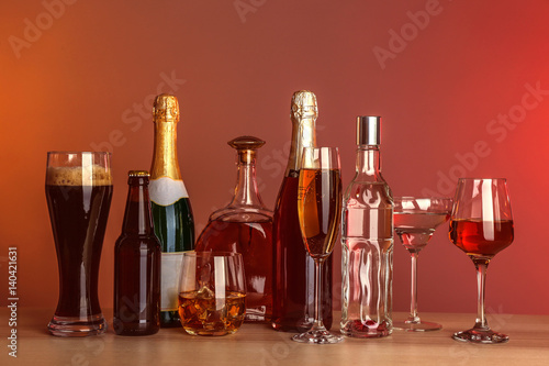 Foto op Plexiglas Bar Table with different bottles of wine and spirits on color background