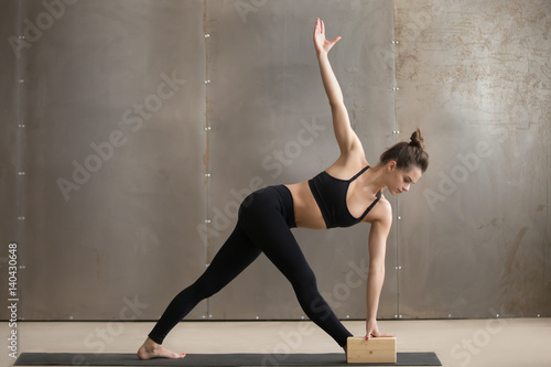 Poster Ecole de Yoga Young attractive yogi woman in black practicing yoga, standing in Utthita Trikonasana exercise using block, extended triangle pose, working out, cool urban style, full length, grey studio background