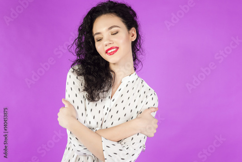 Fotografía  young curly brunette woman hugging herself on a pink background