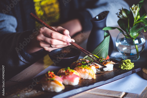 Poster de jardin Sushi bar Man eating sushi set with chopsticks on restaurant