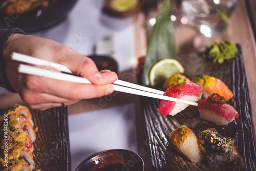 Hands eat sushi with chopsticks