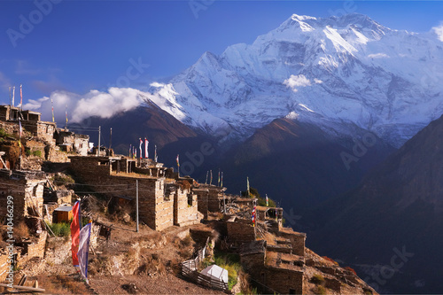 Poster Marron chocolat nepalese village on Pisang region with buddhist praying flags and North Face of Annapurna II mountain summit on background, Annapurna Circuit Trek, Himalaya, Nepal, Asia. horizontal view